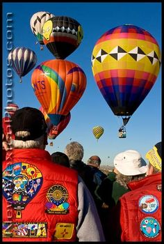 Onlookers at the Balloon Fiesta watch as hot air balloons compete in the key grab. New Mexico PhotoJournal has a new look, a ne. The Balloon, Hot Air Balloon, Flying Without Wings, Albuquerque Balloon Fiesta, New Mexico, Rainbow Colors, Abundance, Balloons, Rest