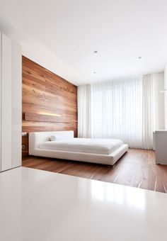 Simple bedroom. Very minimal, only feature is the wood panels on the wall and floor. Add character and texture to the room. Sunlight further highlights these aspects to create an airy and bright room.