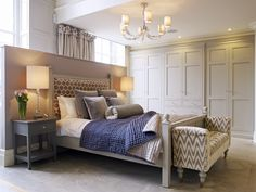 Furniture design, Richard Mason. Interior Design, Jo Batterham, both at The Secret Drawer. Walls, ceiling, panelling Skimming Stone. Wardrobes, Bed, footbench, Purbeck Stone. Bedside tables, Moles Breath, Bed wall Dove Tail. All colours Farrow & Ball.