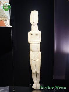 De Amorgos Principios del período de las Cícladas II, 2800-2300 a.C. Esta estatua única de tamaño natural está modelada por su escultor en un estilo bastante bidimensional, conforme a la tipología de figurillas Cicládicas de mármol más pequeñas del mismo período. La figura femenina desnuda con los brazos cruzados debajo de los senos, levantada sobre las puntas de los dedos de los pies, se parece mucho a las figuras femeninas más pequeñas que acompañaron a los muertos en la tumba. M.A.N…