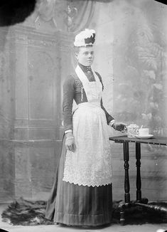 Unidentified woman,wearing apron and cap of a domestic servant, on table to her left is tea cup and pot, ca. 1900