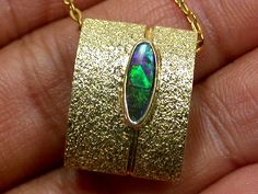MODERN DESIGN BOULDER OPAL 18K GOLD PENDANT SCO967  Origin:	BOULDER OPAL FROM LIGHTNING RIDGE  PENDANT Size:	18 X 14 X 7 MM  Opal Size:	10 X 4 MM  Treated/Untreated:	UNTREATED  Metal:	JEWELLERY IS 18K GOLD STAMPED HALLMARK 750.