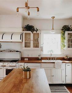 White boho kitchen with oak work tops. Green plants, porcelain sink.