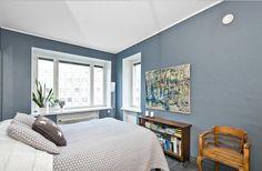 Vaalea makuuhuone, siniharmaa seinä.
