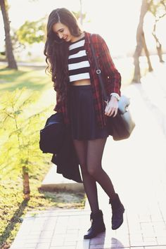 Plaid shirt, striped white & black crop top, black skater skirt, black tights, and black ankle boots.