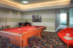 Striped walls and a funky patterned carpet set the stage for this fun game room. Bright red seating matches the mahogany billiard table, while a contemporary bar in the corner houses two swivel chairs with red cushions.
