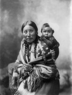 Portrait of Stella Yellow Shirt and baby, Dakota Sioux woman seated, three-quarter length, facing left, with baby on back. Photograph by Heyn Photo, Omaha, Nebraska