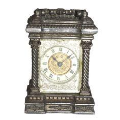PEQUEÑO RELOJ DESPERTADOR Pequeño reloj despertador de viaje en metal plateado, con esfera en porcelana y bronce dorado con números romanos. S.XX. Medidas: 10 x 7 cm.