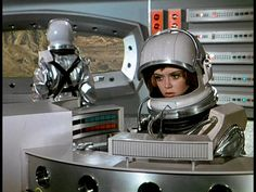 Lt. Ellis and Lt. Harrington tracking inbound UFO about to attack Moonbase. Both are wearing spacesuits in the case of explosive decompression.