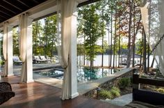The tile of this lakeside saltwater pool was carefully grouped to mimic the color of the nearby lake. Luxurious white outdoor drapery frames the entrway to the nearby outdoor kitchen and lounge and allows for privacy or shade if desired.
