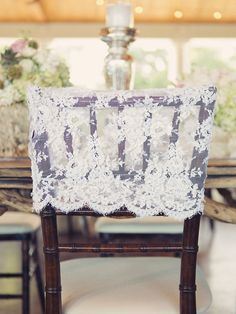 Top your wooden chairs with lace chair caps to complete your romantic vintage wedding theme.     Photo via  Sarah Kate .