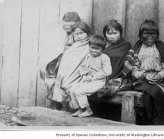 Auk Indian women with painted faces seated on bench next to three children wearing western clothing and blankets, Alaska, ca. 1900 :: Alaska...