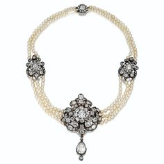 DIAMOND AND PEARL CHOKER-NECKLACE, CIRCA 1880. The center decorated with a floral and foliate cartouche set with old-mine diamonds, anchored by a pear-shaped diamond pendant, the  sides decorated with smaller ornaments of similar design, joining three rows of baroque pearls, the necklace back composed of two rows of pearls completed by a diamond-set floral clasp, the whole set with 207 old-mine and rose-cut diamonds, mounted in gold and silver