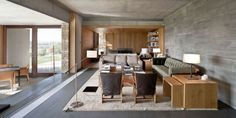 salon moderne en béton et bois clair avec baie coulissante