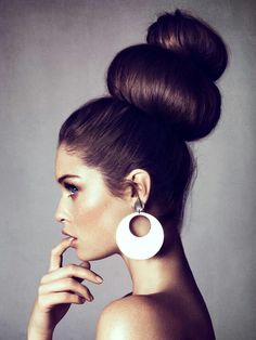 Avant garde hair-style accented with large circle earrings & clever pose by the model.