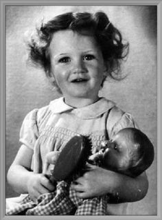 An English girl holding a doll donated from Canada