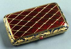 Faberge - A gem-set enameled gold cigarette-case of red guilloche enamel, applied with a gold trellis set with diamonds at the intersections, opaque red enamel borders decorated with gold carnations, cabochon ruby pushpiece - by Carl Hahn, initials CB of workmaster Carl Blank, assay mark of St. Petersburg before 1899, length 3 3/8 inches (8.6 cm)