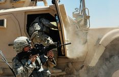 Capt. Zachary Tegtmeier of Naperville, Illinois with the US Army's 82nd Airborne Division uses the door to a M-ATV vehicle to shield him as he returns fire on attacking militants July 2, 2010 over the village of Joikahr, Afghanistan.