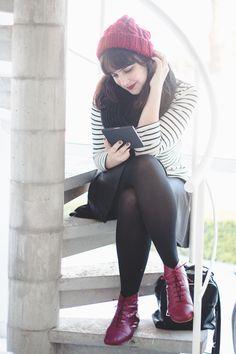 Melina Souza sentada em uma escada espiral lendo em um Kobo (e-reader). Roupa de Outono: blusa listrada branca e preta, saia rodada preta, meia calça preta, botinha de cadarço na cor vinho e gorrinho de tricô vinho.