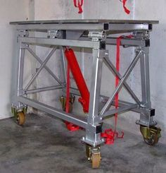 Fold Up Welding Table by chevyman_de -- Homemade fold up welding table constructed from tubing, steel plate, C-channel, casters, steel pins, and a hydraulic cylinder. http://www.homemadetools.net/homemade-fold-up-welding-table