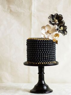 black beaded wedding cake with black, white, and gold flowers