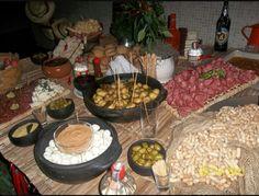 Mesa de comida: azeitonas, amendoins com casca, ovos de codorno e molho, tábua de frios, pães.