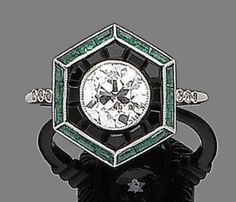 An onyx, emerald and diamond ring  The old brilliant-cut diamond within a millegrain surround of calibré-cut onyx to an outer row of similarly-cut emeralds, diamond approx. 1.10cts Art Deco or Art Deco style.