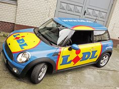 Die Logos wurden so dimensioniert, dass der Lidl Schriftzug in voller Größe zur Geltung kommt. Das ursprünglich weiße Fahrzeug wurde mit einer speziellen 3D Folie in Firmenfarbe vollflächig foliert.
