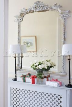 Carved antique mirror with matching lamps and Christmas presents above radiator in London home UK Radiator Cover, Foyer Decorating, Interior Photography, Interior Accessories, Radiators, Home Improvement, New Homes, Carving, Antiques