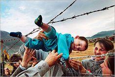 Carol Guzy photograph: the transfer of a child