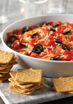 Fiesta Dip — Want to make any fiesta even more festive? This cheesy baked appetizer recipe is made with chicken tossed in hot sauce—then topped with tomatoes and olives.