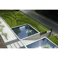 Stairs, clipped boxwood hummocks and two reflecting pools with lillies.