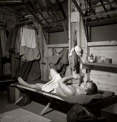 """July 1943. """"Greenville, South Carolina. Air Service Command. A scene in one of the barracks. Enlisted man playing the flute after he has taken a shower."""" Photograph by Jack Delano for the Office of War Information"""