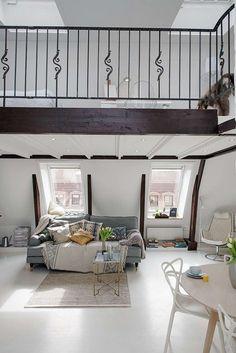 chambre salon 2 en 1 dans un loft à aire ouverte - coin couchage situé au deuxième niveau, canapé gris petit tapis beige et plusieurs coussins