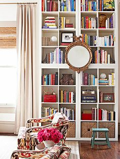 Create the look of custom floor to ceiling library shelving by stacking pre-fab shelving units.
