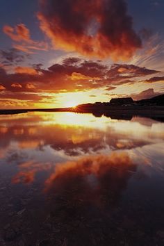 Vibrant yellows, reds and oranges accompany the setting sun as it casts is glow over clouds and water alike Beautiful Sites, Beautiful Sky, Beautiful Lights, Beautiful Landscapes, Natural Mirrors, Sun Painting, 123 Photo, Sunset Images, Dawn And Dusk