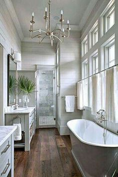 Gorgeous master bathroom. White clean, wood floor, freestanding tub, marble shower