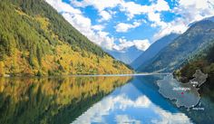 Jiuzhaigou, in remote west China, has inspired dreams of a colorful fairyland among many travelers. Jiuzhaigou features multicolored lakes surrounded by vast mountain forests. These lakes change color throughout the day and year. The colors come from the reflections of surrounding mountainsides and algae and minerals in the lakes.  Fall is the most beautiful season in Jiuzhaigou, when the landscape changes color, providing a vivid backdrop of autumnal hues — an unspoiled, dazzlingly