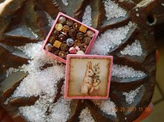 This tiny little box of chocolates is pink and is full of handmade chocolates created by me of polymer clay. Box is 1 square and has an Easter rabbit on top. Chocolates are glued into the box and the lid comes on and off for you to display either opened or closed. Box and contents are not intended for children and animals, as they could pose as a choking hazard