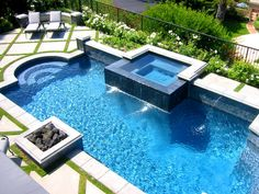 This large swimming pool with water jets includes a built-in hot tub and lava rock fire pit for the ultimate in outdoor relaxing. A nearby lounging area with diagonally set pavers complements the yard's striking geometric design, while verdant grass and white rose borders pop against the glittering blue water.