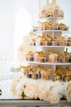 Who doesn't love cute little macarons in clear favor boxes tied up with gold ribbon on a tiered stand surrounded by lush roses and white feathers?