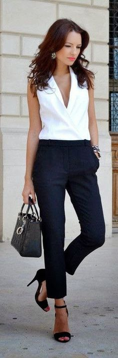 Navy trousers, work pants, and white sleeveless v-neck blouse. Black bag and subtle makeup with black strappy heels.