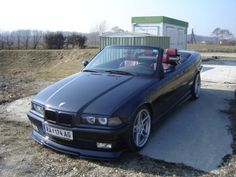 Black BMW e36 Cabriolet with dark red interior and star Porsche-like wheels.