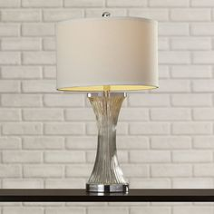 Pairing shimmering details and an imaginative design, this eye-catching Glass Table Lamp with Drum Shade brings statement-making style to your decor. Featuring a concave design and silvery finish, this chic lamp lends an unexpected touch to your home.
