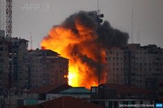GAZA CITY : A ball of fire rises from a building following an Israeli air strike in Gaza City on August 23, 2014. Egypt is to invite Israeli and Palestinian delegations to return to Cairo to resume talks on a long-term truce for Gaza, Palestinian president Mahmud Abbas announced. AFP PHOTO / MOHAMMED OTHMAN