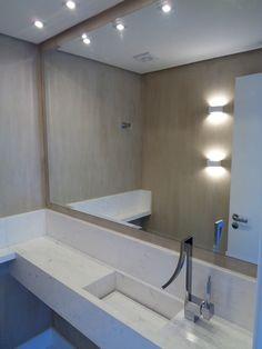 Lavabos | Projetta Arquitetura & Obras Bancada em mármore branco pigues com cuba esculpida e válvula oculta, parede texturato padrão cimento