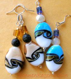 Ohrring mit weiss-brauner ovaler Glasperle: die Schönheit dieses Glassteins wird unterstrichen durch eine runde Lava-Perle und einem bernsteinfarbe...