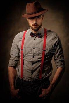 el hombre pasado de moda seria con tirantes vestido con sombrero y pajarita que presenta en fondo os Foto de archivo