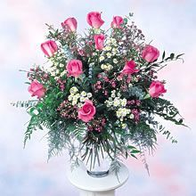 """""""Passionate Pink Roses."""" A dozen pink roses beautifully arranged with complementing wax flower, aster, eucalyptus, and various greens in a glass vase. All arrangements are handmade. Their dimensions and contents may vary."""