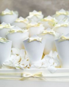 Paper cones with yellow bows held rose petals for guests to toss as the couple leaves the reception